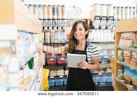 Portrait Of Smiling Female Owner Holding Digital Tablet In Supermarket