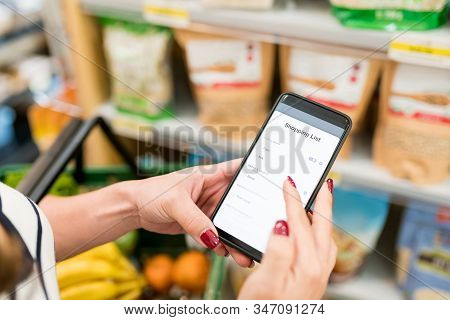 Cropped Image Of Woman Checking Shopping List In Smartphone At Grocery Store