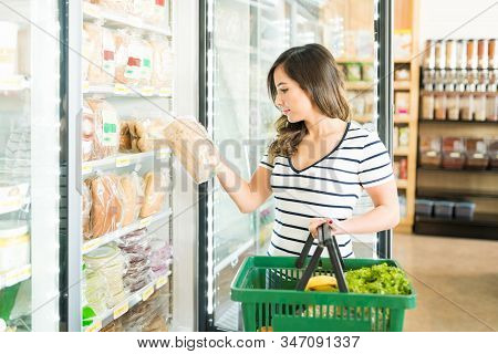 Beautiful Woman Reading Label On Bread While Shopping In Grocery Store