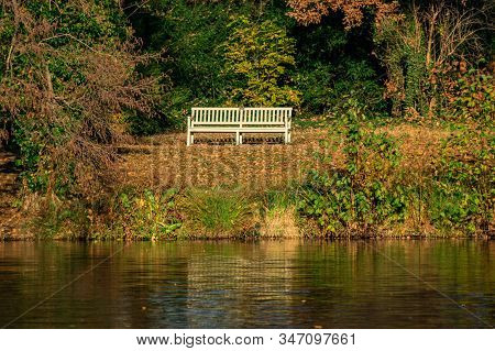 Wooden Bench At Lake Charlottenburg In Berlin In Bright Autumn Sunshine