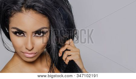 Exotic woman with wild thick dark hair wearing cat eye makeup style