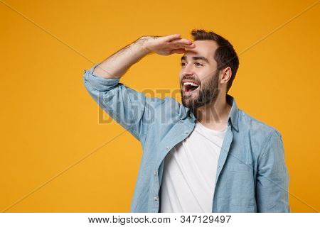 Cheerful Young Bearded Man In Casual Blue Shirt Posing Isolated On Yellow Orange Background In Studi