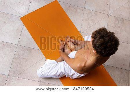 Top View Of Sporty Man Practicing Hatha Yoga In Studio. Male In White Pants Meditating And Holding H