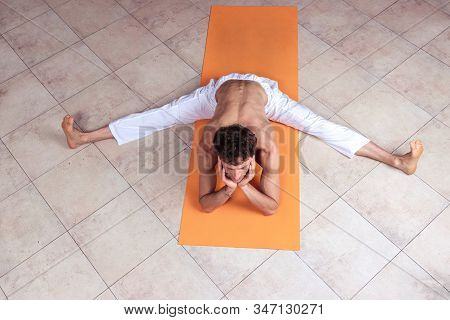 Sporty Man Practicing Hatha Yoga In Studio, Male With Naked Torso In White Pants Staying In Upavisth