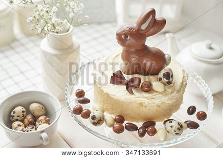 Rustic Easter Cake With Chocolate Bunnies And Eggs. Easter Greeting Card Background, Closeup With Co