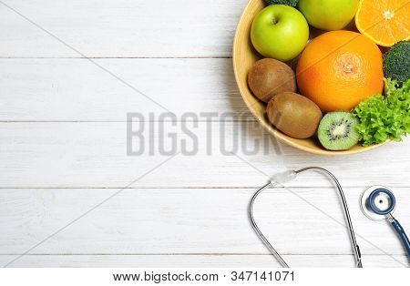 Fruits, Vegetables And Stethoscope On White Wooden Background, Flat Lay With Space For Text. Visitin