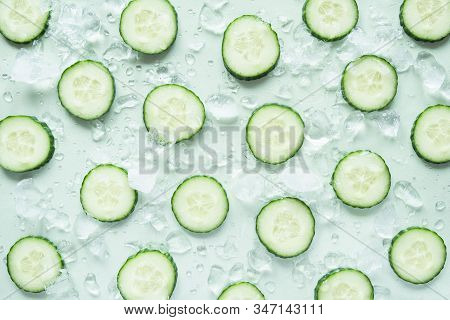 Pattern With Freshly Cut Cucumber Slices And Ice Cubes On Green Background