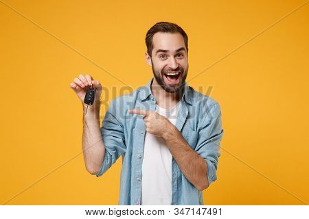 Excited Young Man In Casual Blue Shirt Posing Isolated On Yellow Orange Background, Studio Portrait.