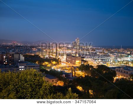Night In The City Of Barcelona In Catalonia, Spain. Columbus Monument And Boulevard Along Port Vell.
