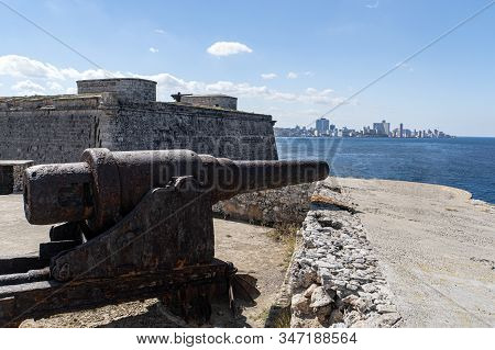 Old Iron Cannons In Front Of Faro Castillo Del Morro Lighthouse