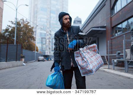 Bearded tramp man with bag on city street