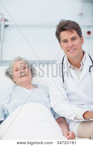 Doctor and patient on the bed looking at camera in hospital ward
