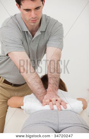Woman lying forward while a physiotherapist massaging her back in a room