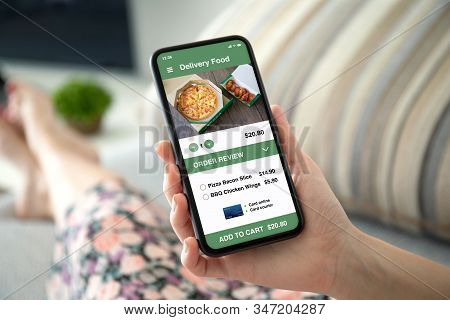 Female Hand Holding Phone With App Delivery Food On Screen In The Room