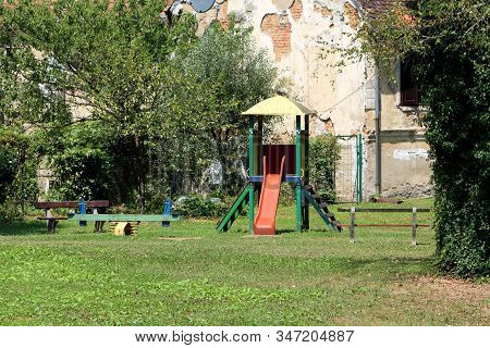 Old Colorful Outdoor Public Playground Equipment In Shape Of Seesaw And Small House With Climbing St
