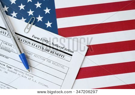 I-797c Notice Of Action Blank Form Lies On United States Flag With Blue Pen From Department Of Homel