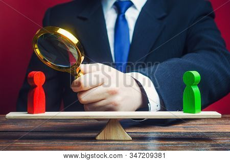 Businessman Is Studying A Red Opponent On Scales. Research And Strategy Development, Management Plan