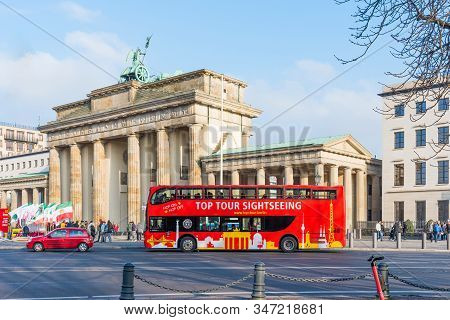 Berlin, Germany - November 23, 2019: The Brandenburg Gate And Bus City Tour In Berlin. Red Sightseei