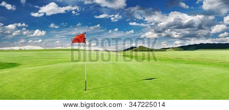 Panorama of golf course with red flag in a hole