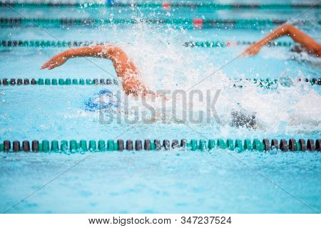 Motion blurred swimmers in a freestyle race, focus on water drops