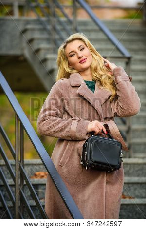 Feeling Warm And Protected. European Winter. Girl Warm Coat Stairs Background. Faux Fur Coat Fashion