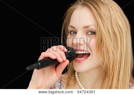 Young blond-haired woman singing against black background