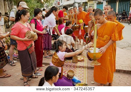 Luang Prabang, Laos - April 15, 2012: Monks Collect Alms And Offerings During Daily Early Morning Pr