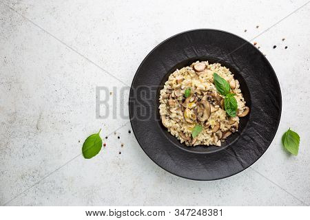 Risotto With Mushrooms In A Black Plate Over White Background, Top View