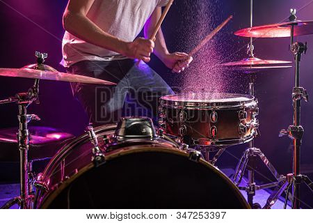 The Drummer Plays The Drums. Beautiful Blue And Red Background, With Rays Of Light. Beautiful Specia