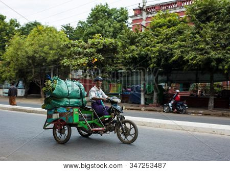 Mandalay, Myanmar - January 3, 2020: Man riding big bags on sidecar motorbike on street with blured background