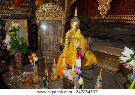 Luang Prabang, Laos - April 16, 2012: Buddha Statues Decorated With Flowers And Gold In A Red Chapel