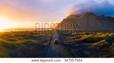 Panorama Of A Gravel Road At A Golden Sunset With Vestrahorn Mountain In The Background And A Car Dr