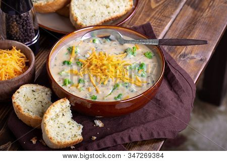 Bowl Of Creamy Broccoli Cheddar Cheese Soup With Toasted Cheese Bread On A Wooden Table