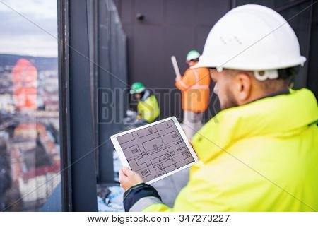 Man Engineer Standing On Construction Site, Holding Tablet.