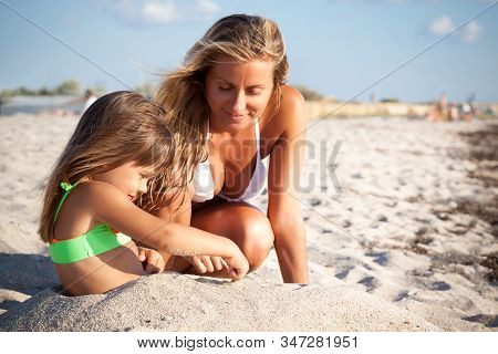 Young Beautiful Blond Woman In White Bikini And Small Girl Sitting And Playing With Sand On Beach On