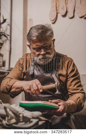 Senior, Bearded Cobbler Repairing Shoe With Hummer In Workshop