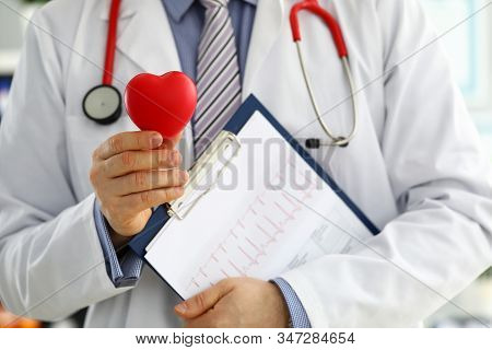 Male Medicine Doctor Hands Holding Red Toy Heart And Cardiogram Chart On Clipboard Closeup. Cardio T