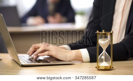 Female Working On Laptop At Office, Hourglass Measuring Time, Efficiency At Work