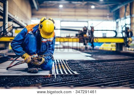 Worker cutting metal, steel with acetylene torch in big factory. Heavy industry, shipyard