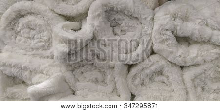 Soft Fluffy White Rugs Folded Into Skeins And Bundles. An Assortment Of Light Bedspreads On A Store