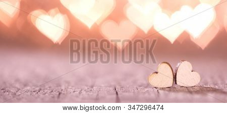 Two handmade wooden hearts on beautiful pink bokeh background. Vintage style. Love Valentine's Day concept.