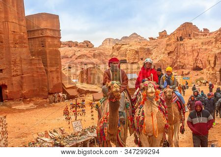 Petra, Jordan - Jan 4, 2020: Bedouins And Tourists Ride Dromedary Camels In Monumental Petra, Unesco