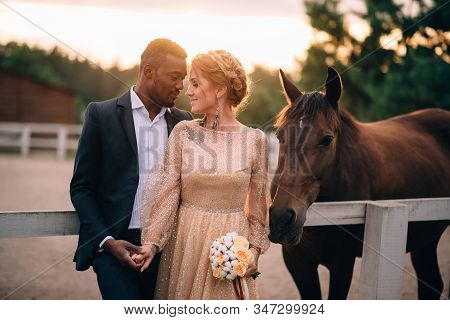 Happy Smiling Newlyweds Standing On Ranch Surrounded By Horses At Sunset
