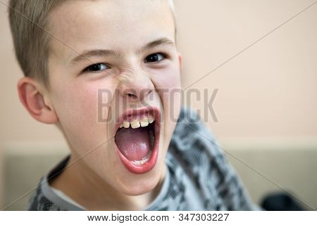 Closeup Portrait Of A Funny Angry Child School Boy With Open Mouth Shouting Angrily.