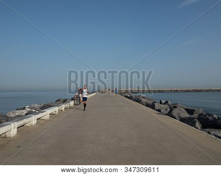 Ostend, Belgium - 7 August 2018: A Runner On The Western Breakwater In Ostend.