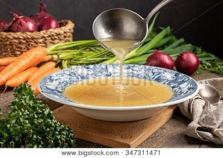 Pouring Chicken Bone Broth From A Ladle Into A Vintage Plate, With Fresh Vegetables In The Backgroun