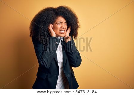 Young beautiful african american business woman with afro hair wearing elegant jacket covering ears with fingers with annoyed expression for the noise of loud music. Deaf concept.