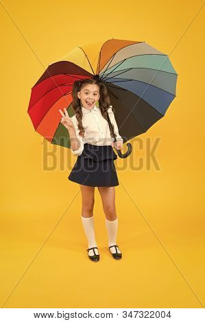Learning Brings You Victory. Happy Small Schoolgirl Celebrating Victory On Yellow Background. Little