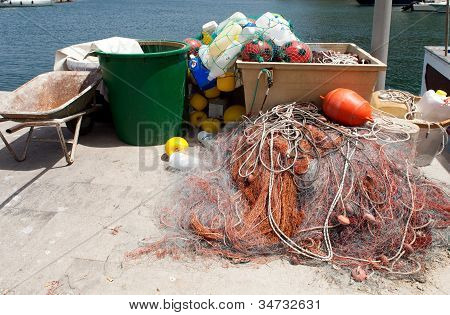 Fish nets and various plastic recipients used by the fishermen like floaters helping to point the nets in the sea. poster