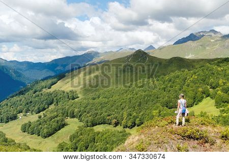 Woman With A Blue Backpack Over A Mountain Valley Gorge. It Is The Caucasian Mountains. The Border O